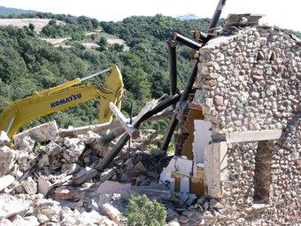 Una màquina enderroca una de les construccions ÀREA D'ESPAIS NATURALS DE LA DIPUTACIÓ