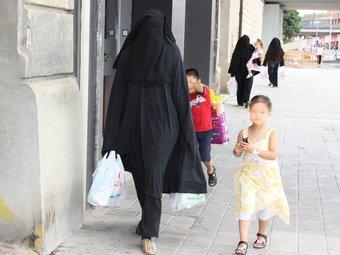 Tres dones musulmanes amb burca a Lleida, caminant amb menors per un carrer de la ciutat ACN