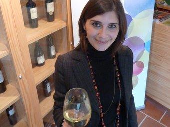 Lara aixeca una copa de vi davant d'un plafó on es veu el logo del nou consorci. G.A
