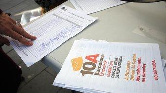 Una taula de recollida de vot anticipat amb el registre dels DNI de la gent que ha votat i un tríptic de la consulta sobre la independència de Catalunya ORIOL DURAN