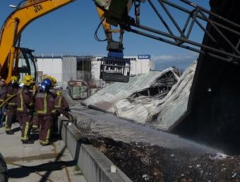 Els bombers remullaven la zona on hi havia cartrons acumulats ahir al matí C. MORELL