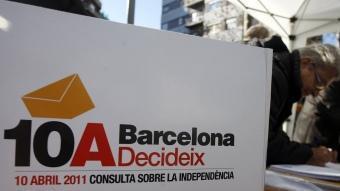 Una persona vota en una de les parades de recollida de vot anticipat al carrer que s'organitzen a la ciutat de Barcelona ORIOL DURAN