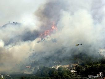 Un helicòpter s'acosta a les flames, el passat dissabte. EFE