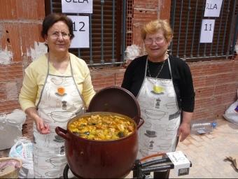 Dues dones de Villar mostren el contingut del perol en que s'ha cuinat l'Olla Xurra. ESCORCOLL