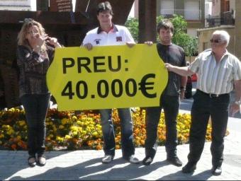 El candidat de CiU, Guillem Mateo, i part de la llista al costat del monument i del rètol que va penjar ahir amb el preu que diu que Pineda ha pagat. EL PUNT