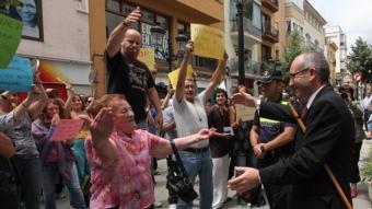 El nou alcalde, Josep Marigó, felicitat per una veïna i escridassat pels indignats. EDDY KELELE /CLICK ART FOTO