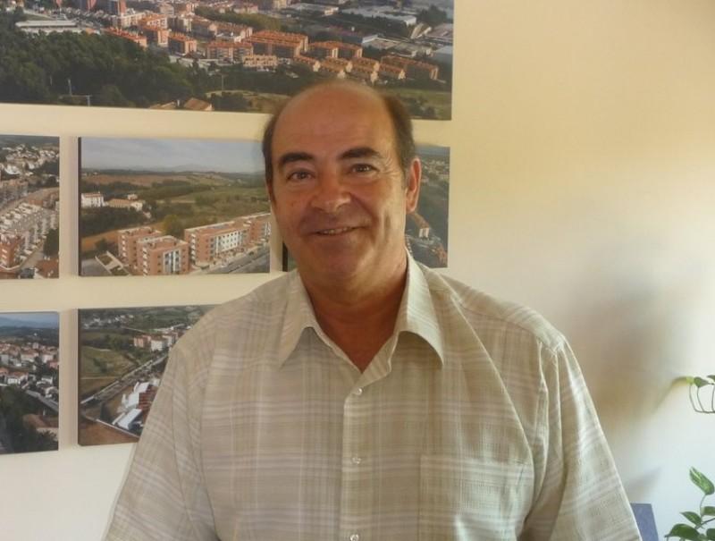 Ramon Mayoral , al seu despatx, amb diverses imatges aèries de Polinyà al fons M.C.B