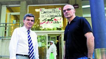 Joan B. Casas, degà del Col·legi d'Economistes de Catalunya i José García Montalvo, catedràtic de l'UPF davant un CAP del Raval amb un cartell en contra de les retallades.  JOSEP LOSADA