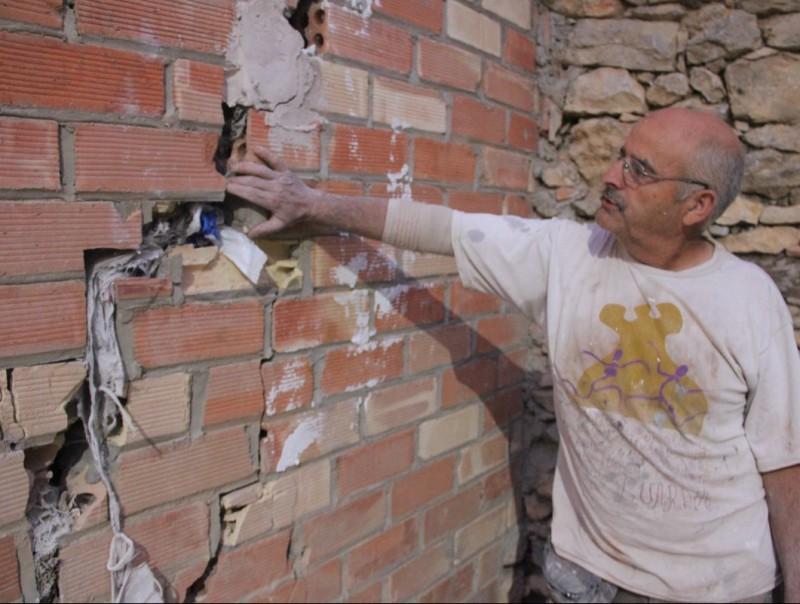 Jordi Elies mostra una de les esquerdes produïdes en la paret d'una granja a Guàrdia de Noguera. D.M