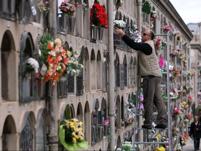 Un home posa flors al cementiri del Poble Nou