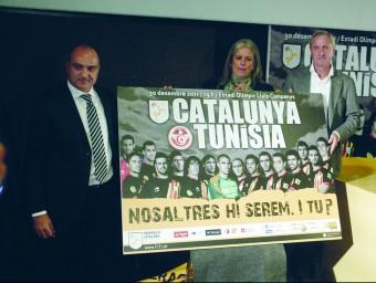 Subies (esquerra) amb Cruyff i Maite Fandos davant el cartell de presentació del partit del 30 de desembre. QUIM PUIG
