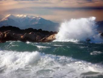 El fort onatge, amb muntanyes nevades al fons, ahir a l'Escala. A la dreta, una benzinera inutilitzada pel vent al Port de la Selva i una tanca doblegada a Sort MANEL LLADÓ / ACN