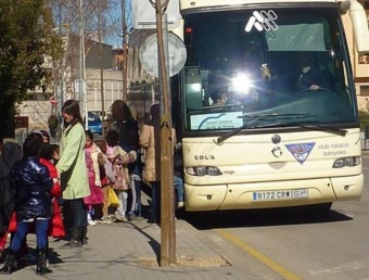 Alumnes pujant a un autobús escolar gestionat pel Consell Comarcal del Pla de l'Estany. R. E