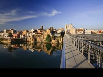 El pont penjant és un dels símbols de la ciutat, que es reflecteix en les aigües tranquil·les de l'Ebre. MARIANO CEBOLLA / PATRONAT TURISME AMPOSTA