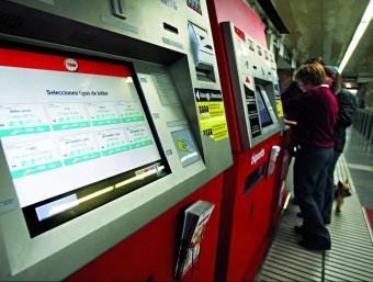 Usuaris del metro adquireixen un bitllet en una màquina. arxiu