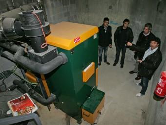 L'alcalde de Vilobí, Francesc Edo (a la dreta), acompanyat dels tècnics a la sala on hi ha la caldera de biomassa de la llar d'infants JUANMA RAMOS