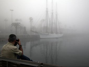 Un home fa una foto de la boira al Port de Barcelona, aquest dimecres ANDREU PUIG