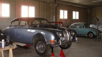 Un Jaguar 3.8 S de l'any 1963, en primer terme, dins les instal·lacions de Serradell Clàssics. J.C