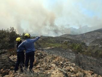 Dos bombers miren el fum que surt de l'incendi de Rasquera EFE