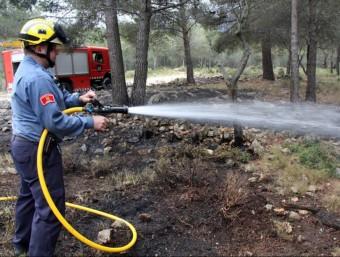 Els bombers voluntaris remullant la zona cremada ACN