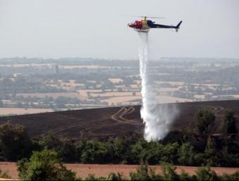 Un helicòpter dels bombers remullava ahir la zona cremada a causa de l'incendi dels Prats de Rei L. BUSQUETS / ACN