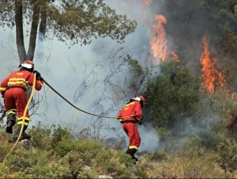 Dos bombers, intentant apagar el foc a la localitat de Carlet EFE