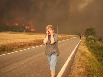 Una dona de Biure fuig de les flames. Al fons, un mosso corre per ajudar un altre afectat pel sinistre LLUÍS SERRAT