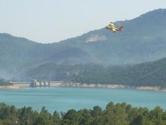 Un hidroavió que participa en les tasques d'extinció del foc, sobrevola aquest dimarts el Pantà de Boadella