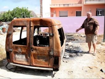 Un dels afectats mostra la furgoneta calcinada. ACN