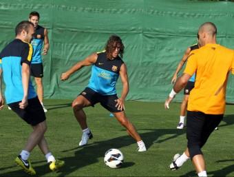 Iniesta, Puyol i Valdés participen en un rondo en la sessió preparatòria d'ahir a la tarda a la ciutat esportiva. FCB