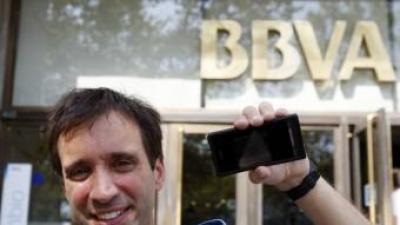 Jordi Abelló, ahir, al davant de la seu del BBVA, a la plaça Catalunya de Barcelona, un dels punts on es pot veure l'exposició al telèfon mòbil. ORIOL DURAN