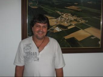 Alfons Soler, al costat d'una fotografia aèria del seu poble, a l'edifici de l'Ajuntament de Viladasens. J. FERRER