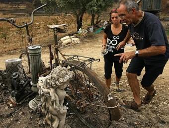 Un veí de Capmany neteja la seva parcel·la i explica la seva situació a Clara Tresserras, de l'associació de les llums que ajuda a les famílies afectades per l'incendi. MANEL LLADÓ