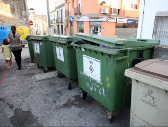 Diversos contenidors de rebuig i orgànica, en primer pla, i de paper i envasos, al fons, a un carrer de Vidreres. LLUÍS SERRAT