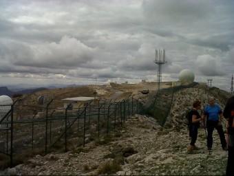 Uns militars vigilen els concentrats a les tanques de la base de la serra Aitana. EL PUNT AVUI