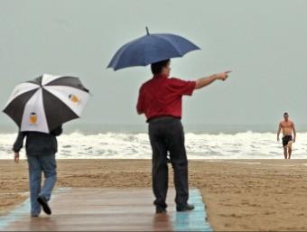 Un pare passeja amb el seu fill per la platja mentre un banyista surt de l'aigua. MANUEL BRUQUE - EFE