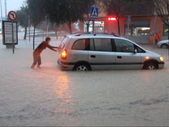 Una dona empeny un vehicle atrapat per les inundacions l'avinguda Barcelona de Tortosa ACN