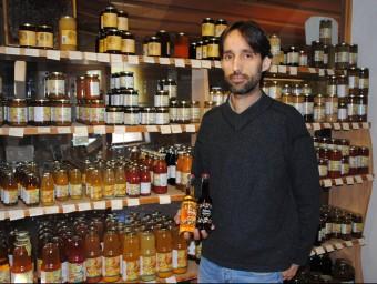 Rubén Valls, davant una mostra dels productes que ven l'empresa i ensenyant dues ampolles del nou suc amb bombolles.  J. TORT
