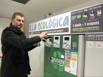 Jordi Pita diposita un envàs a una de les màquines compactadores.  JUDIT FERNÀNDEZ