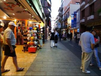 El carrer de Sant Pere de Lloret de Mar, amb turistes passejant i a les botigues, en una imatge de fa dos estius. NURI FORNS