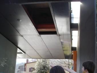 Uns nens el forat que va deixar la placa que va saltar del sostre. TURA SOLER