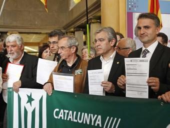 Representants dels ajuntaments barcelonins mostren l'ingrés, a l'esquerra. A la dreta, els gironins presentant documentació M. PÉREZ / M. SABRIÀ