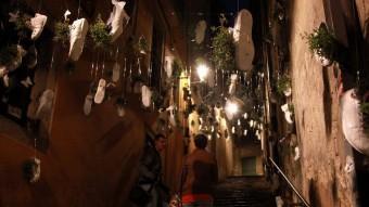 Dos visitants, ahir a la nit al Barri Vell de Girona. El muntatge floral correspon al carrer Miquel Oliva, a prop del plaça del Correu Vell JOAN SABATER