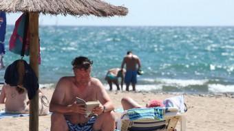 Un estiuejant llegint a la platja. E.MAGRE
