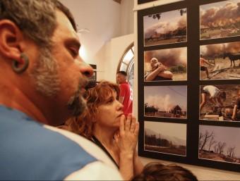 Uns veïns comenten les fotografies de l'exposició de fotografies dedicada als incendis de l'estiu passat i inaugurada ahir a Darnius LLUÍS SERRAT