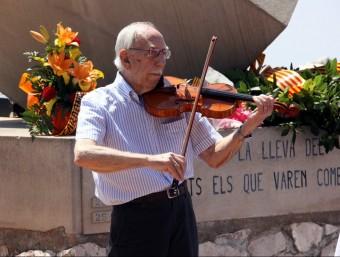 Un dels supervivents toca el violí davant el monument per la Pau. ACN
