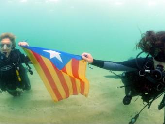 Dues submarinistes sostenen una estelada a sota l'aigua, aquest dissabte a Mataró