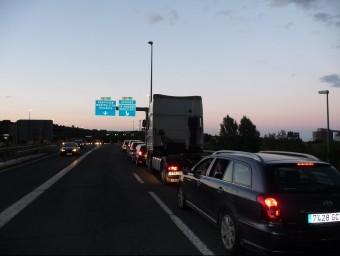 Una llarga cua de vehicles davant el peatge del Voló, esperant per incorporar-se a l'autopista. ESTEVE CARRERA