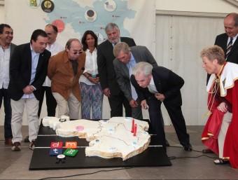 El president de la Federació d'Hostaleria de les comarques gironines, el conseller, i altres representants del sector turístic i de l'administració, al voltant del pastís d'aniversari. JOAN SABATER