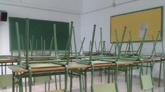 Aula buida de l'institut Josep Maria Llompart, de Mallorca. Al costat, un professor posa deures als alumnes per compensar que ahir tampoc no hi va haver classe R. G. A